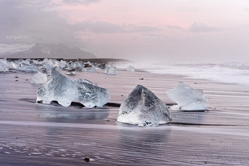 Morgenlicht am Eisstrand | Eisblöcke liegen malerisch an einem schwarzen Vulkanstrand, die Bewegung der Wellen ist zu sehen (Langzeitbelichtung), darüber ein bewölkter Himmel mit roten Farbtönen des Sonnenaufgangs und Nebelschwaden - Location: Island, Jökulsarlon (Jökulsárlón)