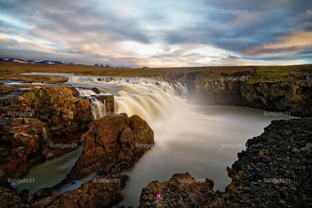 Wasserfall in wilder Landschaft im Abendlicht | Wilder Wasserfall in einer weiten Landschaft zum Sonnenuntergang, Wasserbewegung und Wolkenzug werden durch Langzeitbelichtung betont - Location: Island, Hochland
