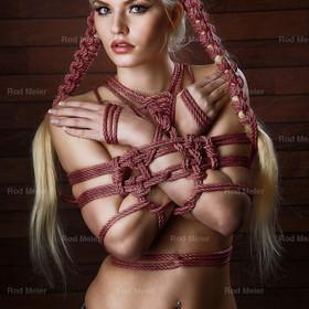 Haar Bondage, 2 Zöpfe - Fine Art of Bondage | Model Michelle-Angelique mit den Armen und Händen an den Körper gebunden. Cooles Haarbondage mit 2 Zöpfen aus rotem Seil - Fine Art of Bondage