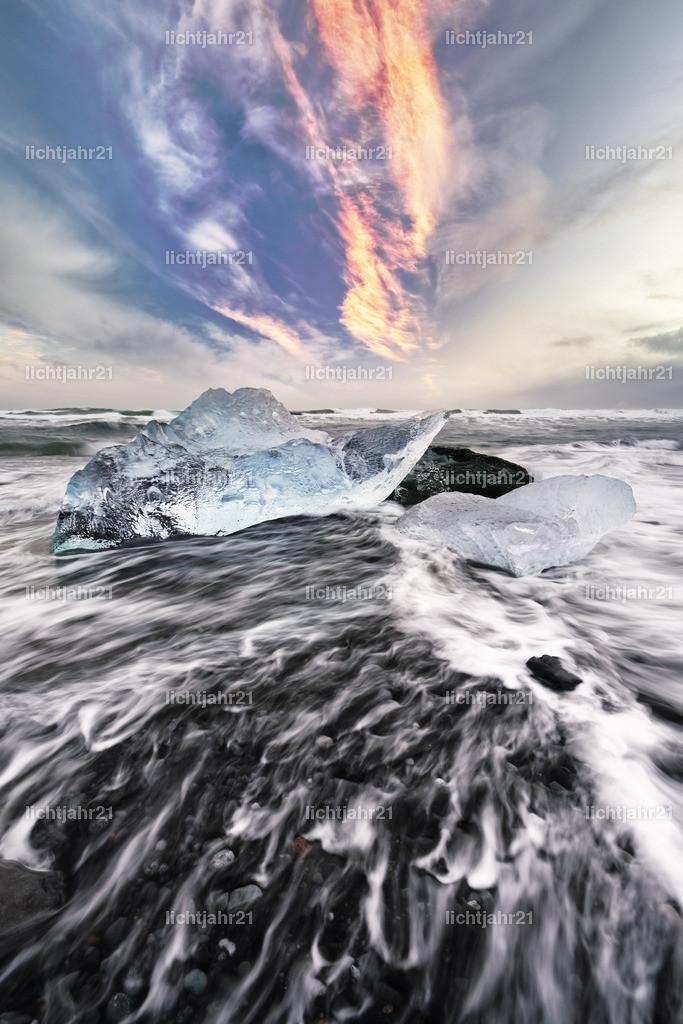 Eisblöcke und Wellen   Eisblöcke an einem Strand mit starker Brandung, die Dynamik einer Welle ist zu sehen (Langzeitbelichtung, Bewegungsspuren), darüber markante vom Abendlicht rötlich gefärbte Wolken - Location: Island, Jökulsarlon (Jökulsárlón)